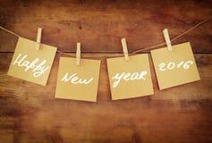 新年快乐卡片在晒衣夹垂悬在木背景 免版税图库摄影