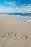 新年快乐在海海滩的2014个季节概念与太阳光芒 库存图片