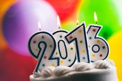 新年快乐在蛋糕的2016个生日蜡烛 库存照片