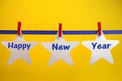 新年快乐横跨白色星和红色钉被写的消息问候在垂悬从钉的蓝色圆点丝带在线 免版税库存照片