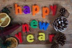 新年快乐磁铁在木背景的概念上写字 库存图片