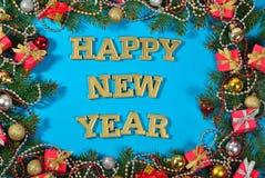 新年快乐金黄文本和云杉的分支和圣诞节装饰 免版税图库摄影