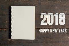 新年快乐2018年和布朗笔记本开放在木桌backg 免版税库存照片