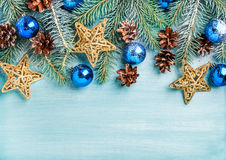 新年或圣诞节背景:冷杉分支,蓝色玻璃球,锥体,在绿松石木背景的金黄星 库存图片