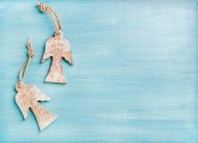 新年或圣诞节背景:在蓝色的两个木天使绘了背景,拷贝空间 免版税图库摄影