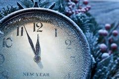 新年时钟搽粉与雪。 库存图片