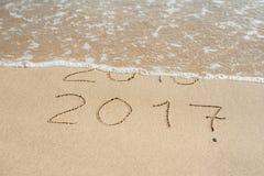 新年2017年是以后的概念-在海滩沙子的题字2016年和2017年,波浪几乎包括数字2016年 免版税库存照片