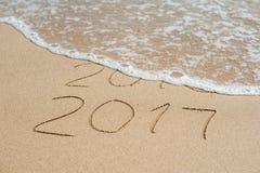 新年2017年是以后的概念-在海滩沙子的题字2016年和2017年,波浪几乎包括数字2016年 库存照片