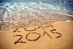 新年2015年是以后的概念-在海滩沙子的题字2014年和2015年 库存照片