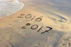 新年2017年是以后的概念-在海滩沙子的题字2016年和2017年 免版税库存照片