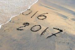 新年2017年是以后的概念-在海滩沙子的题字2016年和2017年 图库摄影