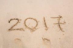 新年2017年是以后的概念-在海滩沙子的题字2017年 库存图片