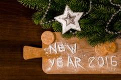 新年曲奇饼和面粉在木背景 库存图片