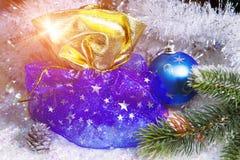 新年有礼物的` s大袋和在雪背景的一个球 库存图片