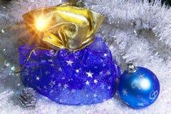 新年有礼物的` s大袋和在雪背景的一个球 图库摄影