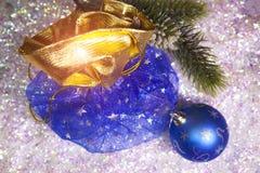 新年有礼物的` s大袋和在雪背景的一个球 免版税库存图片