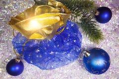 新年有礼物的` s大袋和在雪背景的一个球 免版税库存照片
