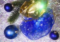 新年有礼物的` s大袋和在雪背景的一个球 库存照片