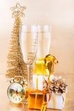 新年构成用香槟和礼物在金背景 免版税库存图片