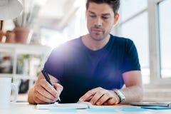 更新他的个人组织者的年轻商人 免版税库存图片
