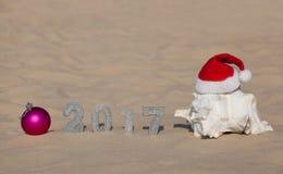新年2017的数字在沙子,并且在沙子附近桃红色球和大白色壳,佩带红色Sa 免版税库存照片