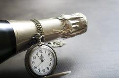 新年的时钟和香槟在午夜 免版税图库摄影