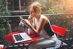 读新闻的美丽的妇女在她的手机,当放松时在观看在便携式的便携式计算机上的影片以后 免版税库存图片