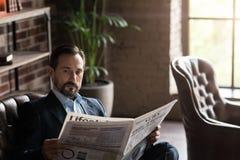 读新闻的英俊的包含的人 免版税库存图片