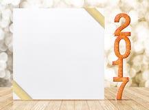 2017新年闪烁数字和白色卡片与金丝带 库存图片