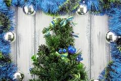 新年题材与蓝色和绿色装饰的圣诞树和在白色风格化木背景的银色球 免版税库存照片