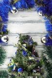 新年题材:与蓝色和绿色装饰的圣诞树和在白色减速火箭的木背景的银色球 库存照片
