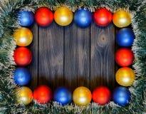 新年题材:圣诞节装饰和球在黑暗的减速火箭的木背景 免版税图库摄影