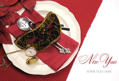 新年餐桌与化妆舞会面具,减速火箭的葡萄酒怀表时钟的餐位餐具 免版税库存图片