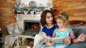 新年` s伊芙,母亲和女儿读了一本书,读圣诞节故事的家庭,坐由壁炉和 影视素材
