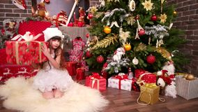 新年` s礼物在妹妹的圣诞树下,从圣诞老人的礼物女儿的,一点的特写镜头 股票录像