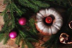 新年` s背景-与一个蜡烛,圣诞树的一块杯形蛋糕 库存图片