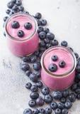 新hommemade乳脂状的蓝莓酸奶用在石厨房用桌背景的新鲜的蓝莓 免版税图库摄影