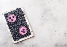 新hommemade乳脂状的蓝莓酸奶用在葡萄酒木箱的新鲜的蓝莓在石厨房用桌背景 顶视图 免版税图库摄影