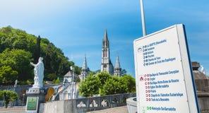 方向的标志在卢尔德前面,法国大教堂的  免版税库存图片
