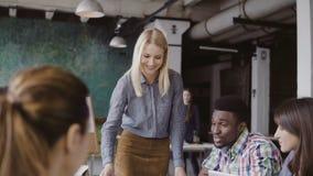给方向的美丽的白肤金发的妇女经理不同种族的队 创造性的业务会议在现代行家办公室 免版税库存照片
