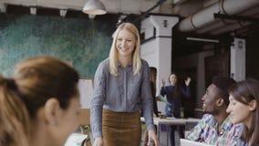 给方向的美丽的白肤金发的妇女经理不同种族的队 创造性的业务会议在现代行家办公室 库存图片