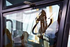 方向盘和杠杆在马达平地机驾驶舱内  免版税库存图片