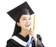 方帽与长袍庆祝的毕业女孩 库存照片