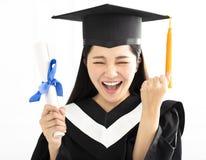 方帽与长袍庆祝的毕业女孩 免版税库存图片