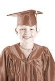 方帽与长袍的儿童毕业生 库存照片