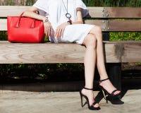 方式和样式 在购物的时兴的女孩休息在一件轻的夏天礼服和一个红色大提包的一条长凳以后 库存图片