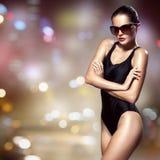方式妇女 比基尼泳装和太阳镜 夜城市背景 免版税图库摄影