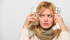 方式感觉更好的快速的流感家补救 女服温暖的围巾,因为病症或流感 女孩举行玻璃水片剂 免版税库存图片