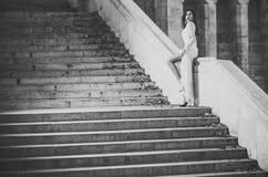 方式纵向 摆在大理石台阶的白色长的礼服的华美的新娘在婚礼前,性感的新娘 免版税库存照片