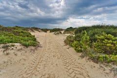 方式通过沙丘在阴沉的天空下 免版税库存图片